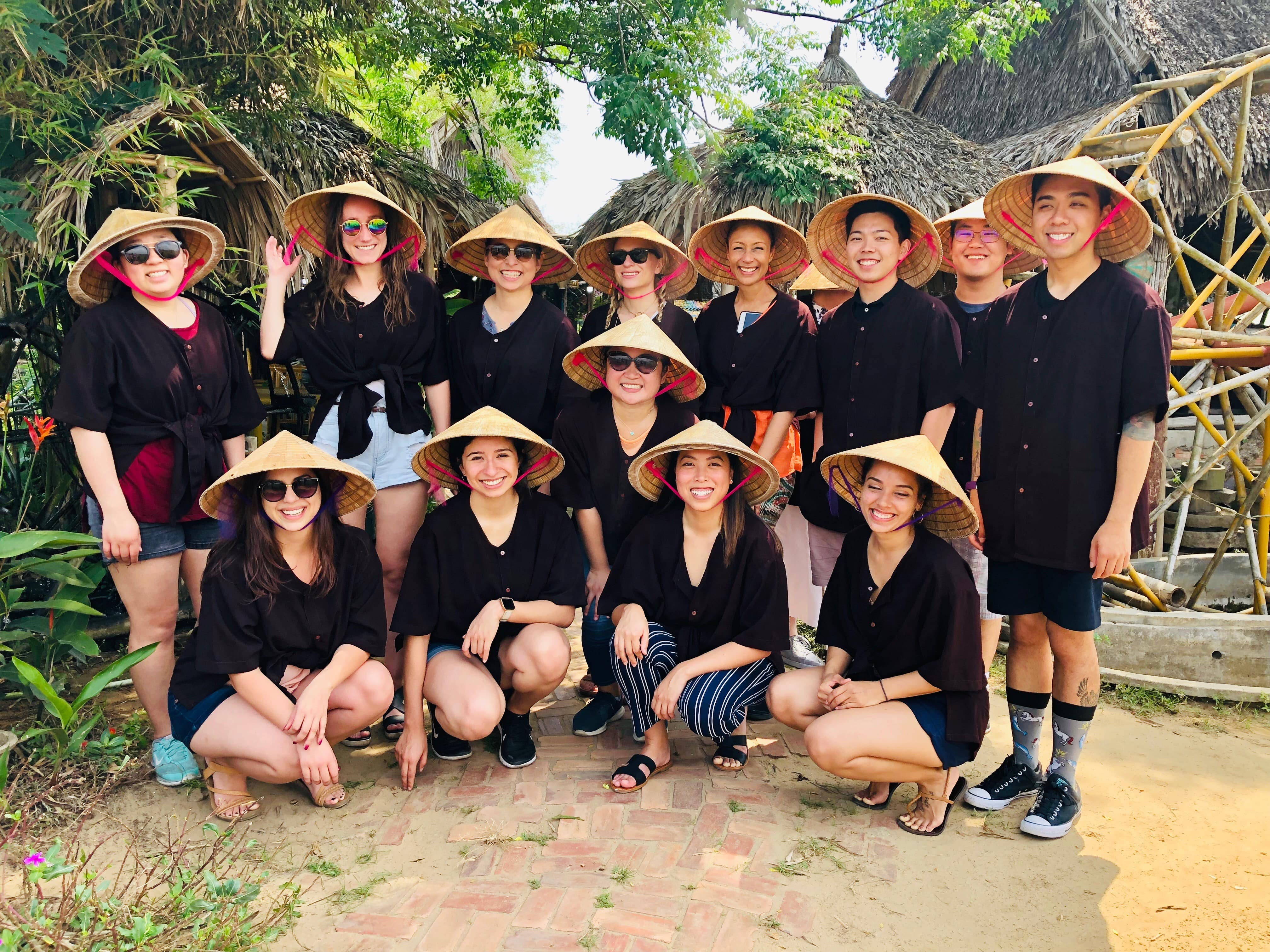 students and faculty on trip in vietnam posing wearing rice hats